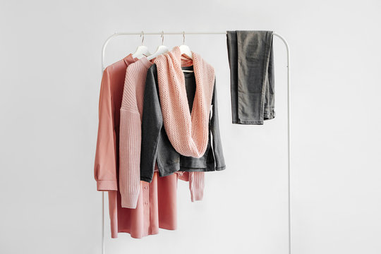 Female clothes in pastel pink and gray color on hanger on white background.  Jumper, shirt, jeans and scarf. Spring/autumn outfit. Minimal concept.