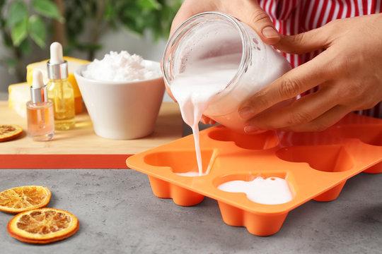 Woman making natural handmade soap at grey stone table, closeup