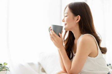 Happy smiling beautiful Asian woman enjoying first morning and smelling aroma of cup of coffee tea in her bedroom.Enjoying free and Relax time, Lazy day off concept.
