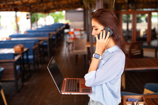 Portrait of female restaurant manager. Businesswoman work with laptop and mobile phone in cafe.