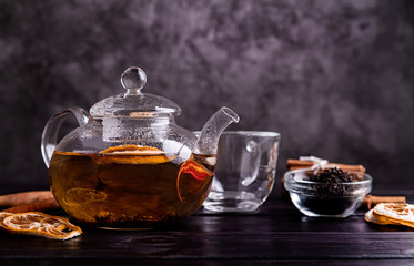 Photo sur Toile The glass teapot of black tea with lemon on dark background