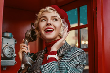 Fashionable happy smiling blonde woman wearing red beret, turtleneck, checkered coat, white wrist watch, talking on the retro phone, posing in red  call box. Copy, empty space for text