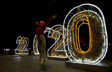 A woman jumps for photo in front of festive illumination lights for the upcoming New Year in Yevpatoriya