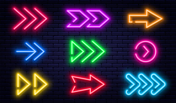 Set of glowing neon arrows. Glowing neon arrow pointers on brick wall background. Retro signboard with bright neon tubes in red, yellow, purple and blue colors