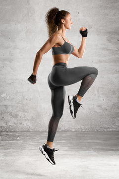 Fitness woman jumping workout. Beautiful athletic girl doing jump