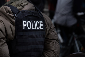 A male police officer dressed in winter clothes stands back on to the camera. A bullet proof vest on his back spells out the word police.