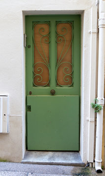 1970s green door with boarded up windows in Provence, France