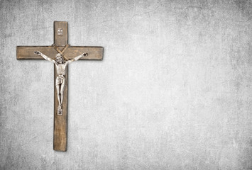 Christian background with crucifix of Jesus Christ on gray distressed concrete wall with copy space