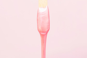 liquid wax for pink depilation drains from the stick. The concept of depilation, waxing, smooth skin without hair.