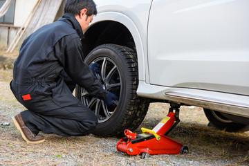 写真素材:タイヤ交換、整備、自動車、オイルジャッキ、作業、男性、作業着
