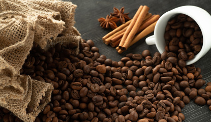 Poster Café en grains Grains of coffee pour out from a white coffee cup on a dark background from a bag with cinnamon sticks and anise stars