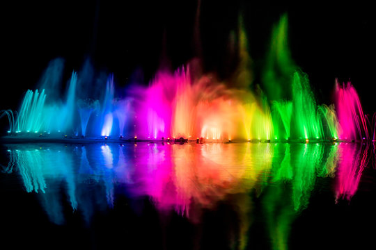 The colorful water fountain dancing in celebration festival refection color on water with dark night sky background