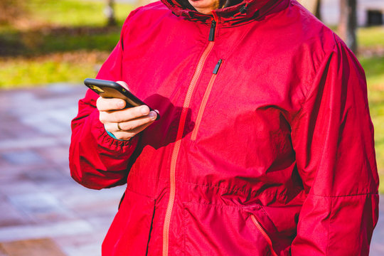 A man in a red waterproof sport jacket stands on the street and looking his phone. Sportsman. Measuring. Distance. Heartbeat. App for sport. Park. Outdoor. Training. Workout. Tracker