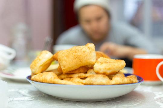 Traditional mongolian food of Baursak. Hand takes food to eat
