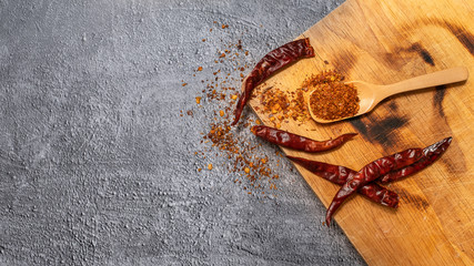 Cayenne pepper in a wooden spoon and dried chillies placed on a wooden chopping board on the cement floor Wall mural