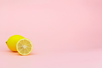 Yellow lemon and part of it on a pink background with place for text
