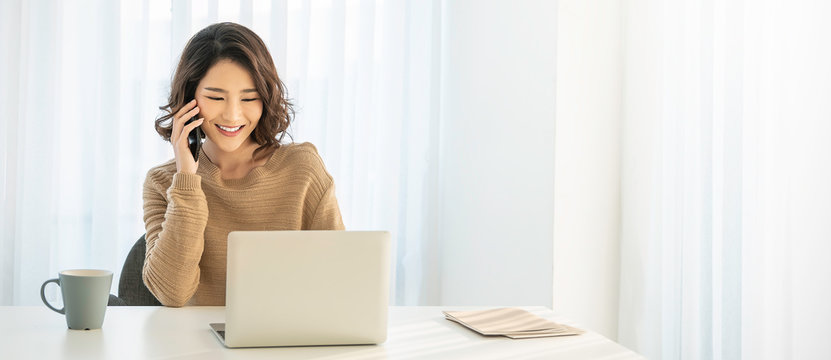 Portrait of young asian business woman talk on smartphone write notebook laptop in home office. Beautiful girl at desk computer take order. Startup business asia woman online telemarketing sme banner