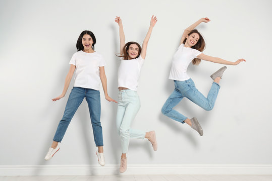 Group of young women in stylish jeans jumping near light wall
