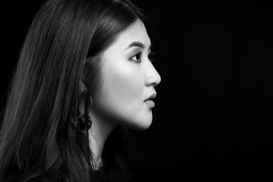 Black and white portrait of young Asian woman on dark background