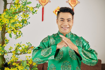 Happy smiling Vietnamese young man in traditional costume making special gesture to wish happy...