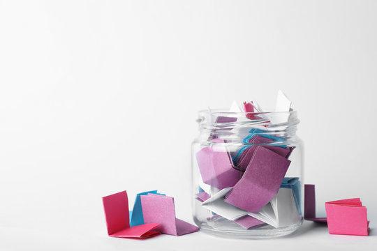 Glass jar full of folded paper sheets on white background