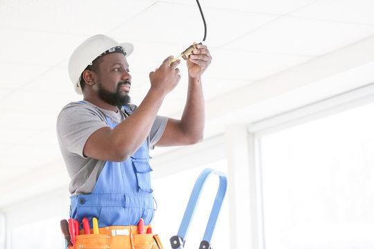African-American electrician performing wiring in room
