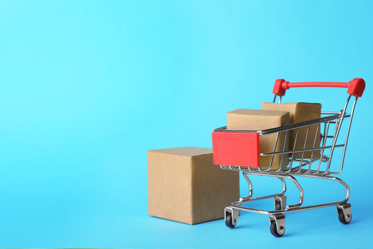 Shopping cart and boxes on light blue background, space for text. Logistics and wholesale concept