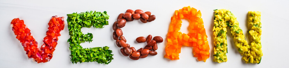 Fototapeta The word vegan on white background, top view. Vegan food concept. Vegan composed of beans, guacamole, vegetables and herbs. obraz