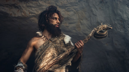 Primeval Caveman Wearing Animal Skin Holds Stone Hammer Stands Near Cave and Looks Around Prehistoric Landscape, Ready to Hunt Animal Prey. Neanderthal Going Hunting into Jungle. Low Angle Shot Wall mural