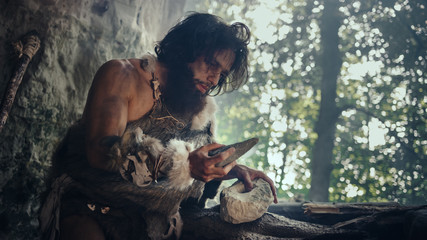 Primeval Caveman Wearing Animal Skin Holds Sharp Stone and Makes First Primitive Tool for Hunting Animal Prey, or to Handle Hides. Neanderthal Using Handax. Dawn of Human Civilization Wall mural