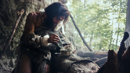 Fototapeta Primeval Caveman Wearing Animal Skin Hits Rock with Sharp Stone and Makes First Primitive Tool for Hunting Animal Prey or to Handle Hides. Neanderthal Using Handax. Dawn of Human Civilization