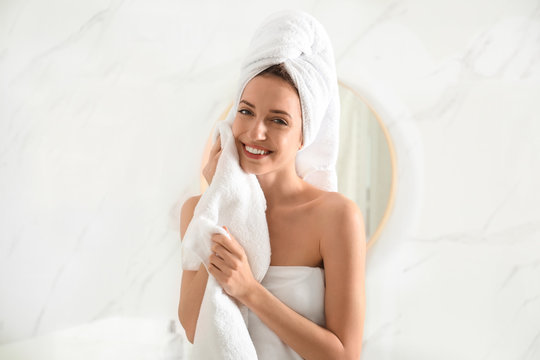 Young woman wiping face with towel in bathroom
