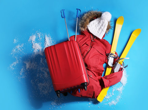 Suitcase with warm clothes and skis on light blue background, flat lay. Winter vacation
