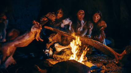 Fototapeta Neanderthal or Homo Sapiens Family Cooking Animal Meat over Bonfire and then Eating it. Tribe of Prehistoric Hunter-Gatherers Wearing Animal Skins Eating in a Dark Scary Cave at Night
