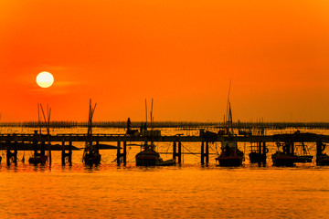 Fotobehang Oranje eclat silhouette sunset at the sea. The way of life of fishermen on the bridge or jetty and returning from fishing from the sea. Chonburi, Thailand 22 Dec 2019.