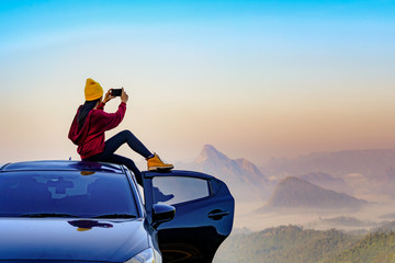 young woman sitting on the car roof with enjoy taking photo with mobile phone to the nature of mist in the mountain at sunrise morning, cheerfully life travel