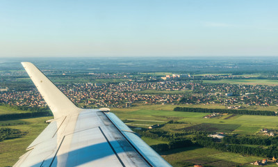 Suburb of a large European city through the porthole of an airplane