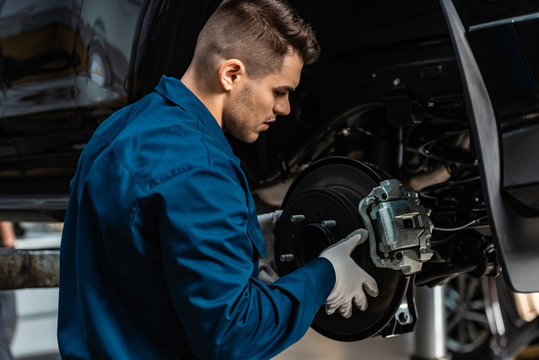 young, attentive mechanic installing disc brakes on raised car