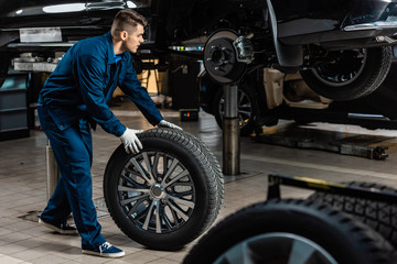 young mechanic holding car wheel near raised car in workshop Fotomurales