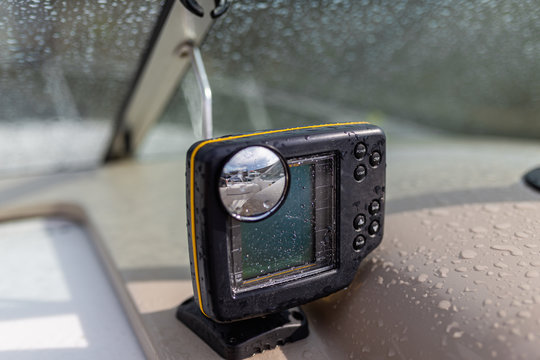 Gps navigation system in raindrops for swimming in the sea located on the dashboard of a pleasure yacht. Close-up black modern chartplotter device on Motor boat dashboard, local time, depth, map, trip