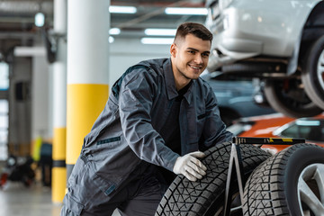 handsome, smiling mechanic holding new tire in workshop