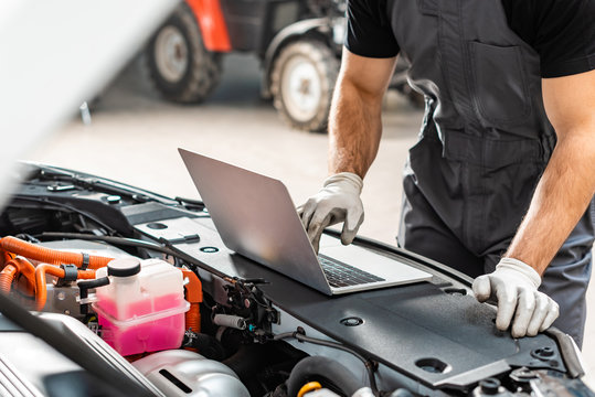 cropped view of mechanic using laptop near car engine compartment