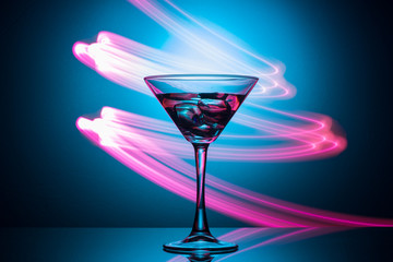 Martini glass with drink and ice, with a spectacular illumination of the background.
