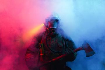 Fototapeta Fireman with axes in the smoke.