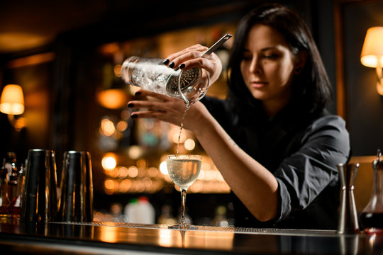 Professional bartender girl pouring a trasparent alcoholic drink from the measuring cup to the glass through the strainer filter