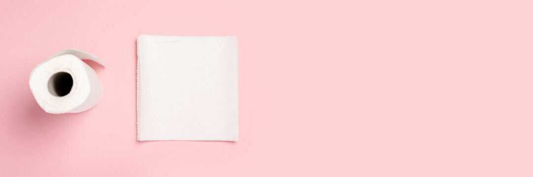 Roll of paper towels and few pieces towels on a pink background. Concept is 100 natural product, delicate and soft. Flat lay, top view. Banner