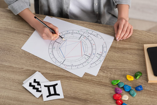 Cropped view of woman drawing natal chart by stones and papers with zodiac signs on table