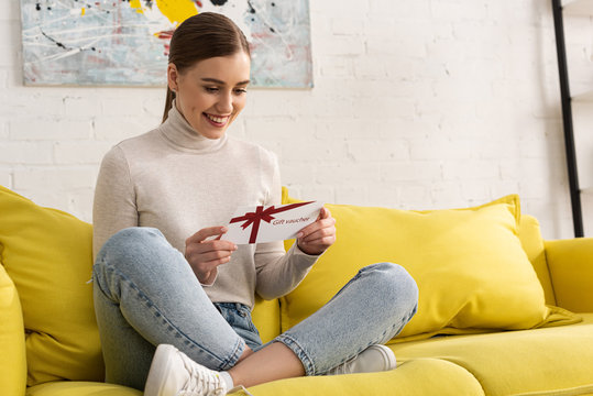 Smiling young woman with gift voucher on sofa in living room
