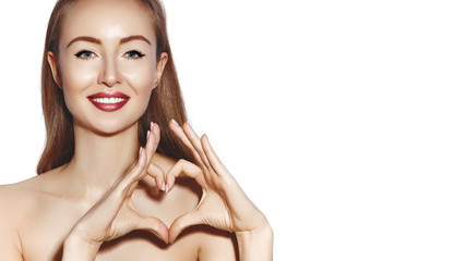 Romantic young Woman making Heart Shape with her Fingers. Love and Valentines Day Symbol. Fashion girl with Happy Smile