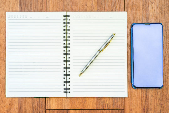 Top view image of open notebook with blank pages and cellphone on wooden table